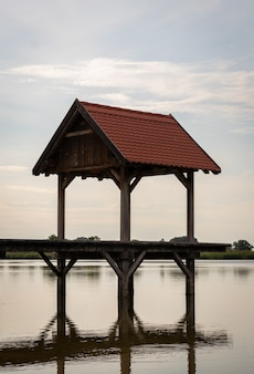 Foto vertical de um mirante em um lago com reflexo na água