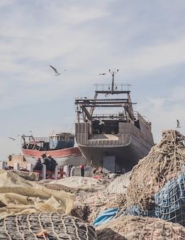 Foto vertical de um navio incompleto próximo a várias redes de pesca com gaivotas voando acima