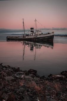 Foto vertical de um navio no mar ao pôr do sol