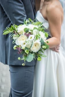 Foto vertical de um noivo romântico e uma noiva segurando um buquê de noiva