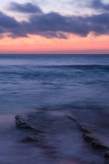 Foto vertical de um oceano calmo com ondas pequenas e um céu nublado laranja