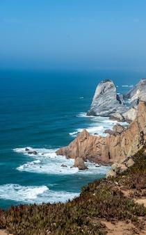 Foto vertical de um oceano com penhascos e rochas na costa