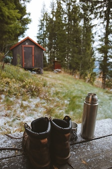 Foto vertical de um par de botas e um frasco perto de uma cabana de madeira na floresta na noruega