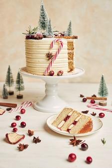 Foto vertical de um pedaço de bolo em um prato e um bolo de natal