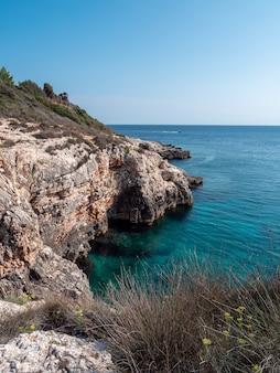 Foto vertical de um penhasco rochoso com um mar azul esverdeado em um fundo de céu claro