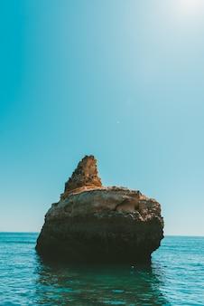 Foto vertical de um penhasco rochoso no mar sob o céu claro