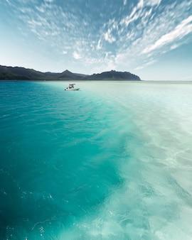 Foto vertical de um pequeno barco viajando pelo lindo oceano durante o dia
