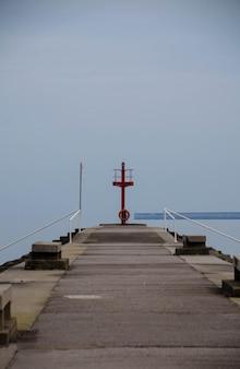 Foto vertical de um píer levando ao oceano sob um céu claro
