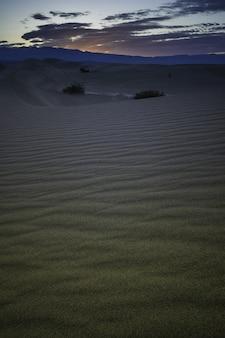 Foto vertical de um pôr do sol de tirar o fôlego sobre a paisagem deserta