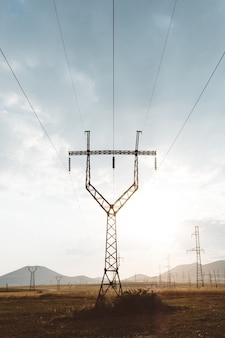 Foto vertical de um poste elétrico com grades de metal no topo sob um céu nublado