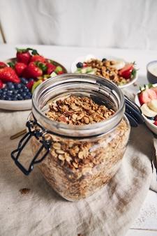 Foto vertical de um pote de granola ao lado de tigelas de frutas, frutas vermelhas e iogurte