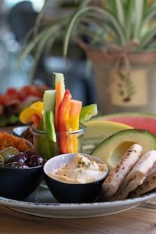 Foto vertical de um prato de comida tradicional etíope, frutas e vegetais em uma mesa de madeira