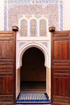 Foto vertical de um prédio com arco na entrada e decorado com mosaicos geométricos