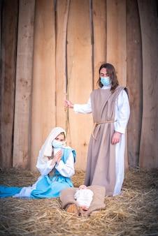 Foto vertical de um presépio com os personagens usando máscaras enquanto adoram o bebê jesus