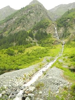 Foto vertical de um riacho fluindo cercado por montanhas verdes com um céu sombrio