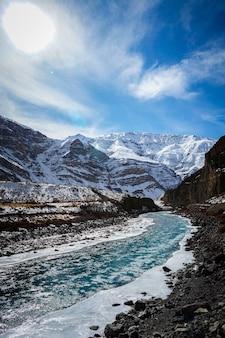 Foto vertical de um rio congelado com montanhas cobertas de neve ao fundo