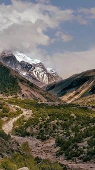 Foto vertical de um rio ganga com montanhas cobertas de neve
