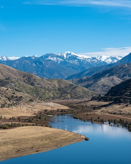 Foto vertical de um rio sinuoso com montanhas majestosas e céu azul