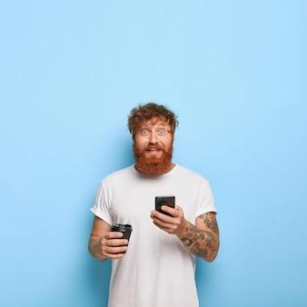 Foto vertical de um ruivo bonito e alegre posando com seu telefone