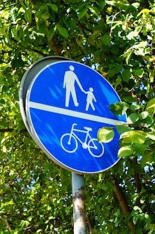 Foto vertical de um sinal azul com ícones de pessoas e uma bicicleta no parque