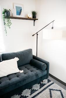 Foto vertical de um sofá e um belo design de uma luminária de chão na sala de estar