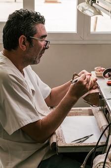 Foto vertical de um técnico de prótese dentária trabalhando em uma oficina.