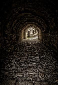 Foto vertical de um túnel vazio em direção aos prédios