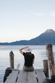 Foto vertical de um turista sentado no cais e apreciando a vista