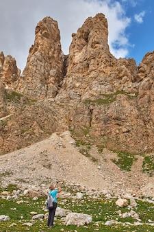 Foto vertical de um turista tirando uma foto de altos penhascos rochosos na itália