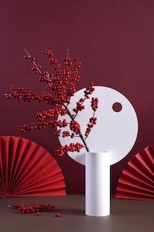 Foto vertical de um vaso decorativo com frutas vermelhas silvestres e leques chineses