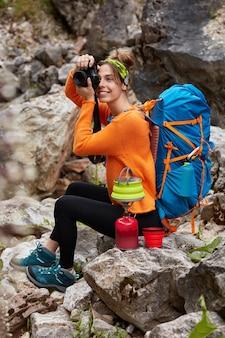 Foto vertical de um viajante alegre sentado nas pedras, tirando fotos maravilhosas com a câmera, fazendo café no fogão de acampamento, usando macacão laranja
