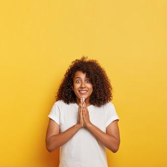 Foto vertical de uma adolescente com cabelos cacheados que surpreendeu o olhar feliz, sorri amplamente, mantém as palmas das mãos juntas em gesto de oração, acredita na ajuda de deus, tem uma expressão esperançosa, usa roupas brancas