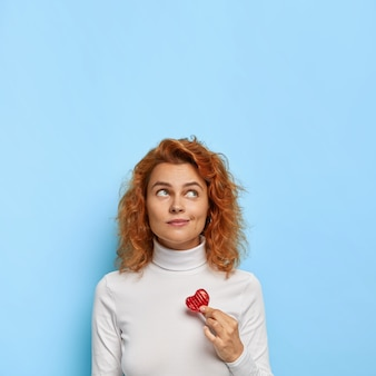 Foto vertical de uma adorável mulher europeia ruiva com olhar pensativo e sonhador acima, segura um pequeno coração em forma de doce, expressa amor por alguém, usa gola alta branca, isolada na parede azul