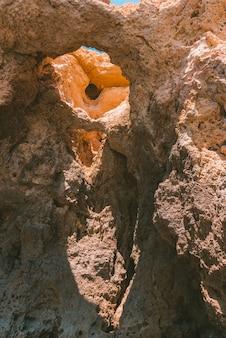 Foto vertical de uma antiga formação rochosa com buracos