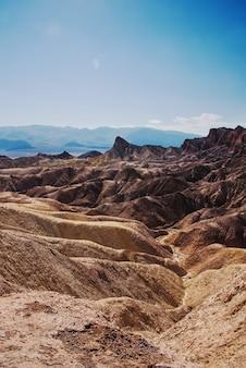 Foto vertical de uma área desértica com colinas rochosas