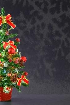 Foto vertical de uma árvore de natal com enfeites vermelhos e um fundo de espaço de cópia cinza
