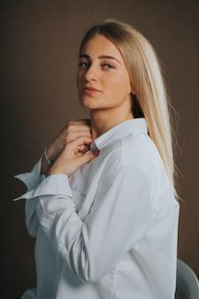 Foto vertical de uma atraente mulher loira, branca, com uma camisa branca, posando em uma parede marrom