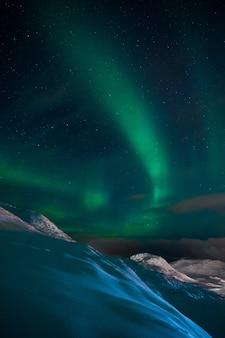 Foto vertical de uma aurora no céu acima das colinas e montanhas cobertas de neve na noruega