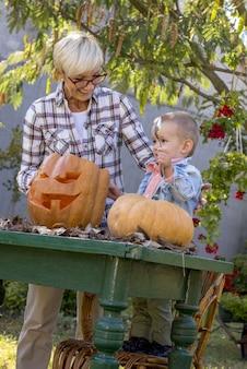 Foto vertical de uma avó ajudando uma criança a esculpir abóboras para o halloween