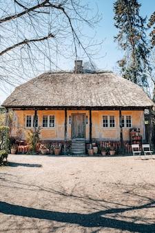 Foto vertical de uma bela casa de aldeia entre as árvores capturada em um dia ensolarado