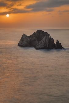 Foto vertical de uma bela costa quebrada durante o pôr do sol na espanha