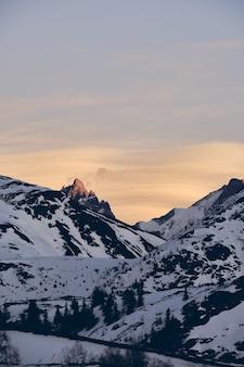 Foto vertical de uma bela montanha alpina coberta de neve