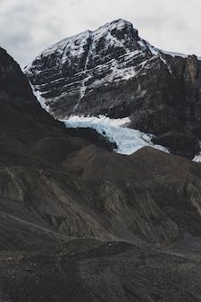 Foto vertical de uma bela paisagem de nuvens sobre formações rochosas cobertas de neve na zona rural