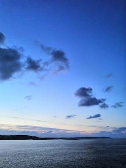 Foto vertical de uma bela praia em malta capturada em um dia ensolarado com colinas no horizonte