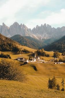 Foto vertical de uma bela vila em uma colina cercada por montanhas
