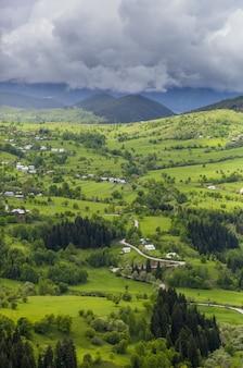 Foto vertical de uma bela vila nas colinas cobertas de grama