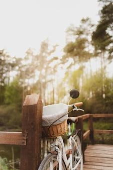 Foto vertical de uma bicicleta estacionada em uma ponte de madeira na floresta