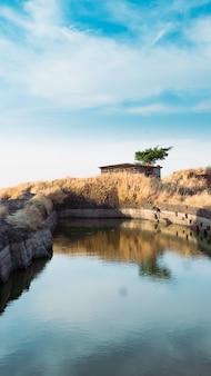 Foto vertical de uma cabana à beira do lago sob um céu nublado