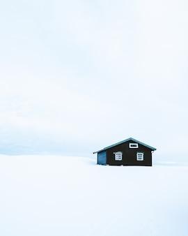 Foto vertical de uma cabana de madeira em uma área nevada na noruega