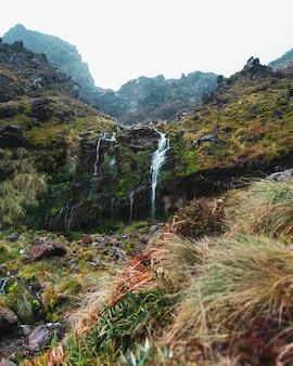 Foto vertical de uma cachoeira em altas montanhas